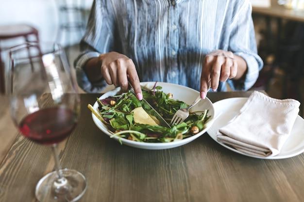 Portret van vrouw handen met mes en vork salade en glas rode wijn eten op houten tafel in restaurant