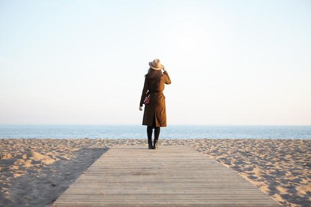 Portret van vrouw het lopen op promenade die blauwe overzees bekijkt die klassieke hoofddeksel en bruine laag draagt