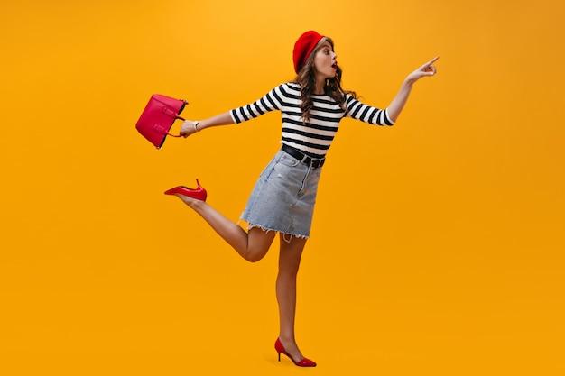Portret van vrouw in gestreept overhemd verrassend poseren op oranje achtergrond. cool meisje in rode baret en trendy rok heeft plezier.