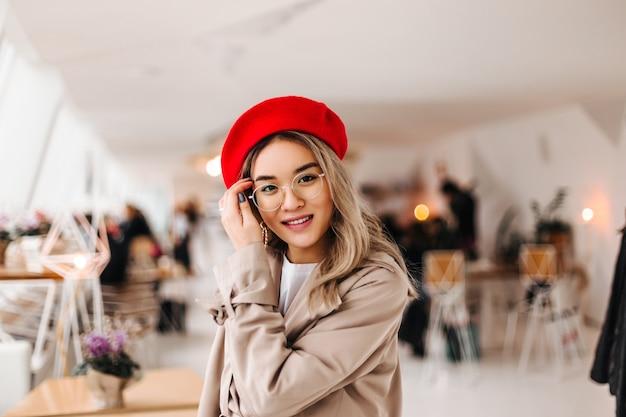 Portret van vrouw in glazen en rode baret