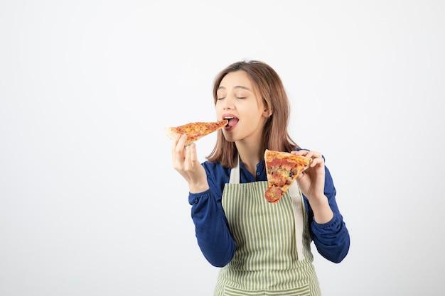 Portret van vrouw in keukenschort die pizza op wit eet