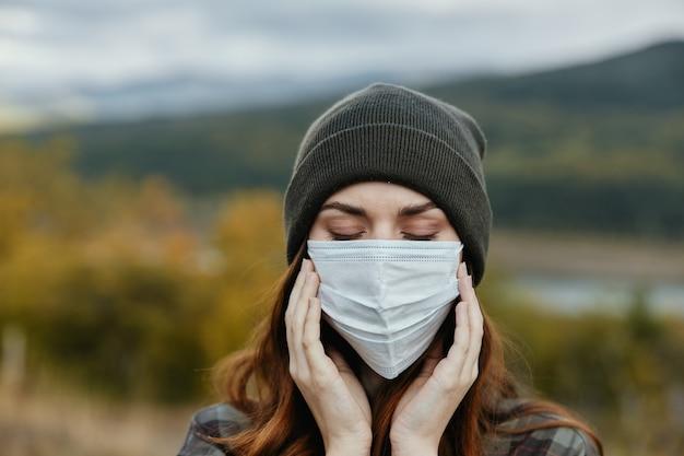 Portret van vrouw in medische masker en warmte hoed natuur herfst bergen.