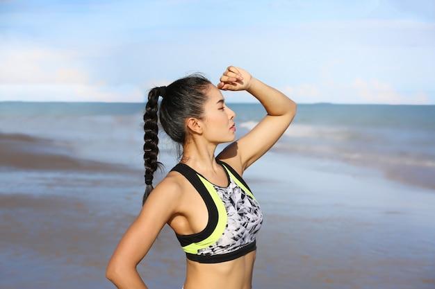 Portret van vrouw in oefeningskleren die en zich aan het overzees op strand bevinden kijken