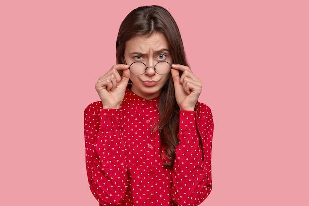 Portret van vrouw in rood overhemd en ronde oogglazen