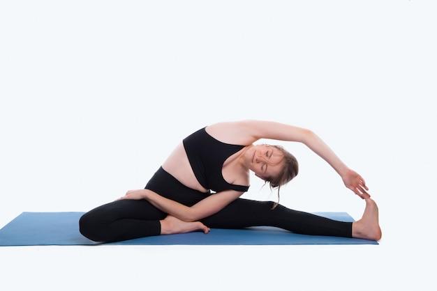 Portret van vrouw in studiou het beoefenen van yoga over witte muur