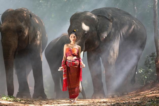 Portret van vrouw in thais traditioneel kostuum met olifanten
