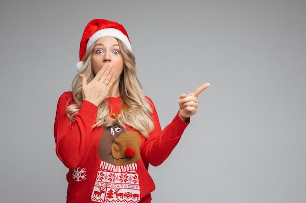 Portret van vrouw in trui en kerstmuts is verrast met iets