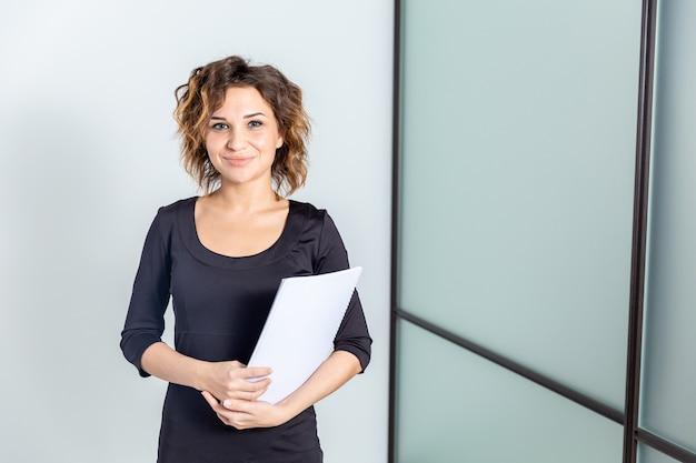 Portret van vrouw in wit bureau met geïsoleerde documenten.