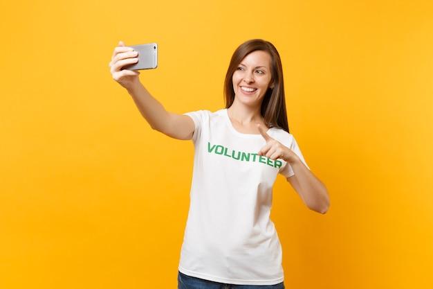 Portret van vrouw in wit t-shirt geschreven inscriptie groene titel vrijwilliger nemen selfie schot op mobiele telefoon geïsoleerd op gele achtergrond. vrijwillige gratis hulp hulp liefdadigheid genade werk concept
