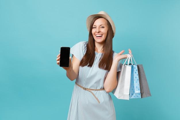 Portret van vrouw in zomerjurk, strohoed met pakketten met aankopen na het winkelen, mobiele telefoon met leeg scherm geïsoleerd op blauwe pastelachtergrond. kopieer ruimte voor advertentie.