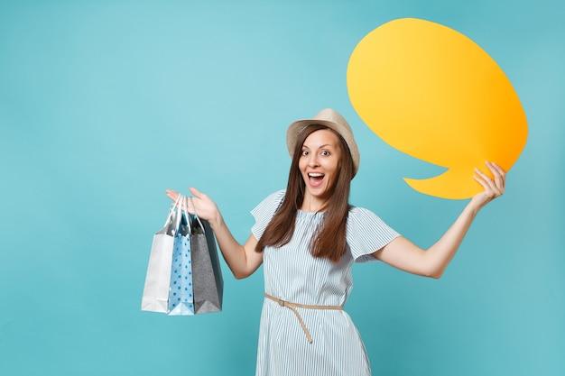 Portret van vrouw in zomerjurk, strohoed met pakketten met tassen met aankopen na het winkelen, lege blanco say cloud, tekstballonkaart geïsoleerd op blauwe pastelachtergrond. ruimte advertentie kopiëren