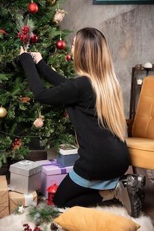 Portret van vrouw kerstboom versieren.