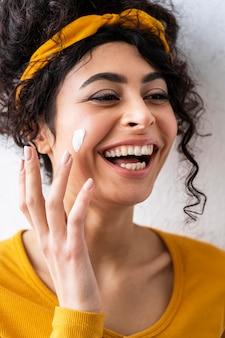 Portret van vrouw lachen en spelen met vochtinbrengende crème