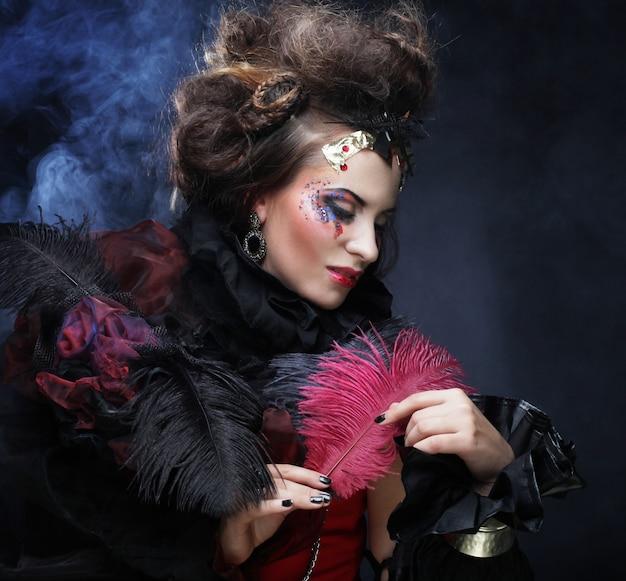 Portret van vrouw met artistieke make-up in blauwe rook