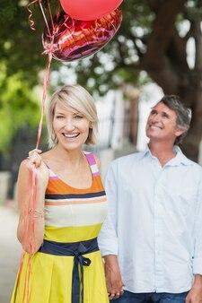 Portret van vrouw met ballonnen en man