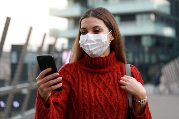 Portret van vrouw met beschermend masker wandelen in de moderne stad met smartphone