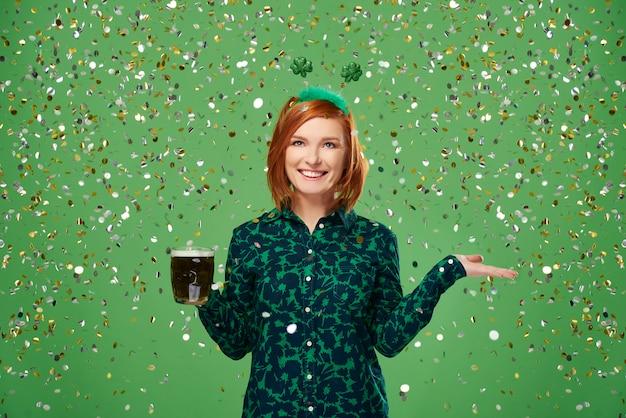 Portret van vrouw met bier onder een regen van confetti