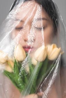 Portret van vrouw met bloemen die in plastic worden behandeld