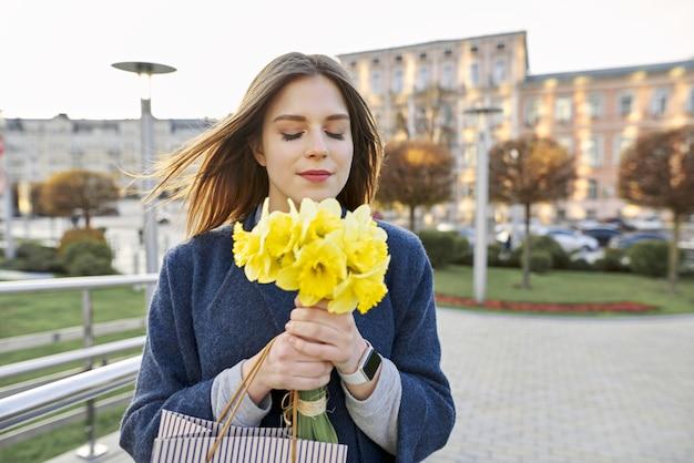 Portret van vrouw met boeket van gele lente bloemen narcissen