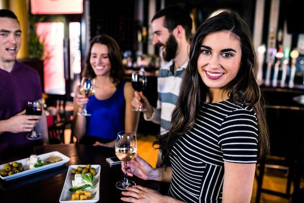 Portret van vrouw met een aperitief met vrienden in een bar