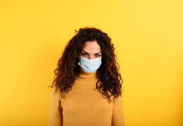 Portret van vrouw met gezichtsmasker tegen covid-19 op geel