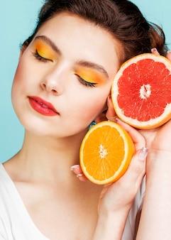 Portret van vrouw met grapefruit en oranje