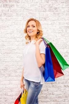 Portret van vrouw met het winkelen packs op de achtergrond van de muur