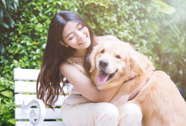 Portret van vrouw met hondgolden retriever in park met zonsondergang deur