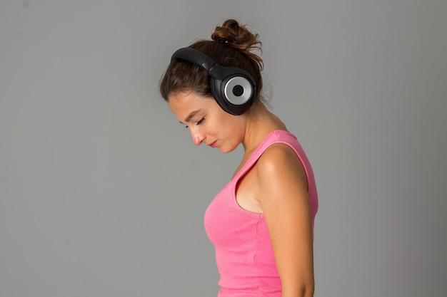 Portret van vrouw met hoofdtelefoons in studio op grijze muur