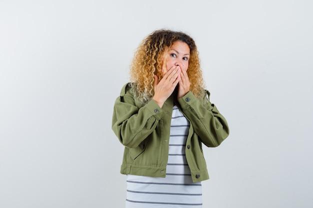 Portret van vrouw met krullend blond haar die handen op mond in groen jasje houden en geschokt vooraanzicht kijken