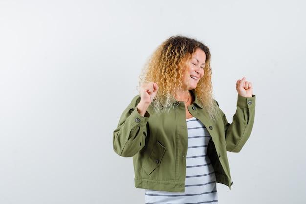 Portret van vrouw met krullend blond haar die winnaargebaar in groen jasje tonen en zalig vooraanzicht kijken