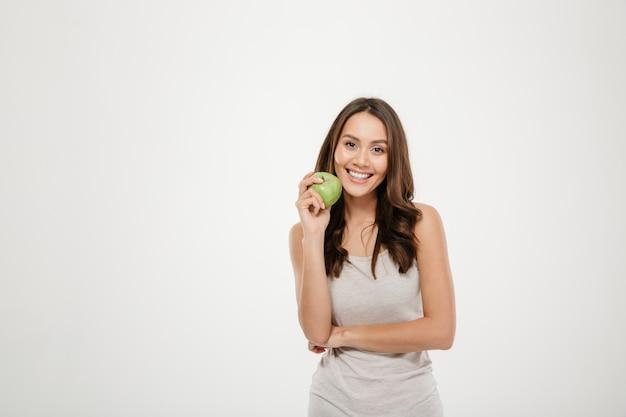 Portret van vrouw met lang bruin haar die op camera met groene in hand appel kijken, die over wit wordt geïsoleerd