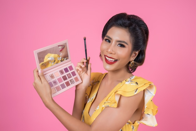 Portret van vrouw met make-upborstel en schoonheidsmiddel