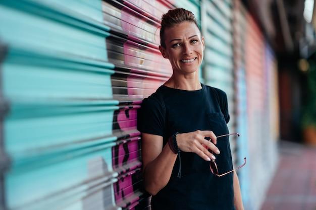 Portret van vrouw met mohawkkapsel die zich tegen garagedeur bevinden