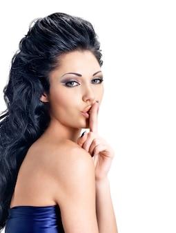 Portret van vrouw met stilte uitdrukking. foto van donkerbruin meisje met vinger dichtbij lippen, concept van stilte