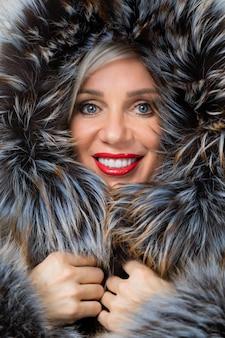 Portret van vrouw op middelbare leeftijd in modieus jasje met bont dat op grijs wordt geïsoleerd