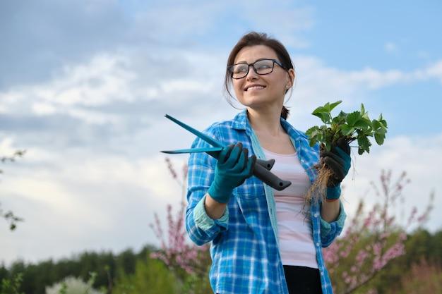 Portret van vrouw op middelbare leeftijd in tuin met hulpmiddelen, aardbeistruiken