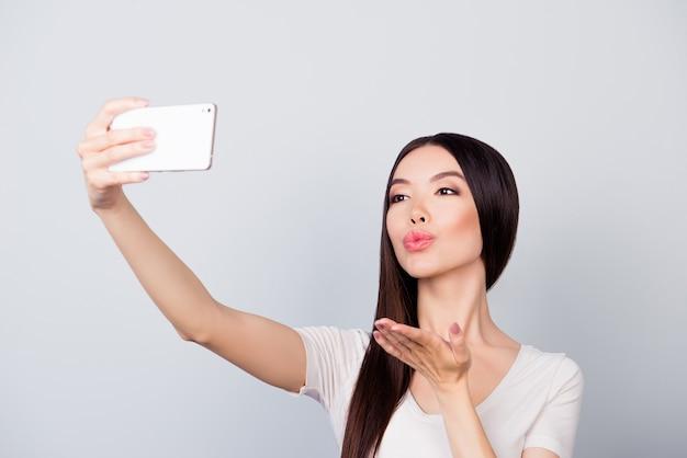Portret van vrouw selfie nemen en kus verzenden close-up