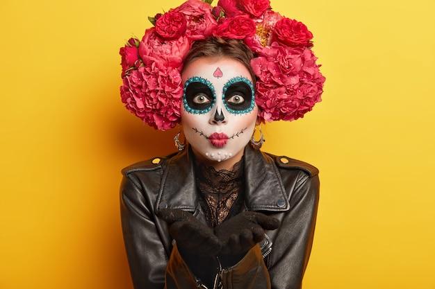 Portret van vrouwelijk keurig skelet bereidt zich voor op mexicaans carnaval, blaast luchtkus, draagt schedelmake-up, gekleed in zwarte jas, heeft enge blik, geïsoleerd op gele achtergrond. bodypaint en gezichtskunst