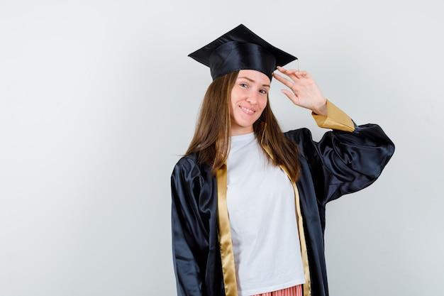 Portret van vrouwelijke afgestudeerde die groetgebaar in uniforme, vrijetijdskleding toont en vrolijk vooraanzicht kijkt