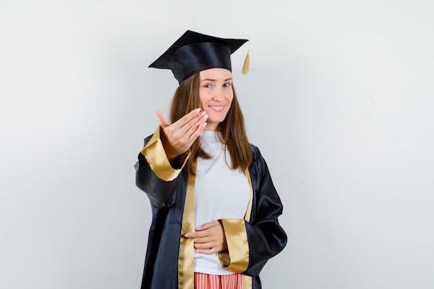 Portret van vrouwelijke afgestudeerde die uitnodigt om in academische kleding te komen en vrolijk vooraanzicht kijkt