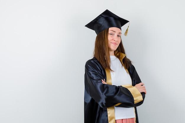 Portret van vrouwelijke afgestudeerde permanent met gekruiste armen in uniforme, vrijetijdskleding en op zoek naar zelfverzekerd vooraanzicht