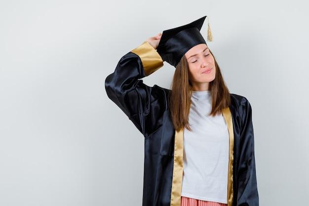 Portret van vrouwelijke afgestudeerde poseren met opgeheven hand op het hoofd in uniforme, vrijetijdskleding en op zoek charmant vooraanzicht