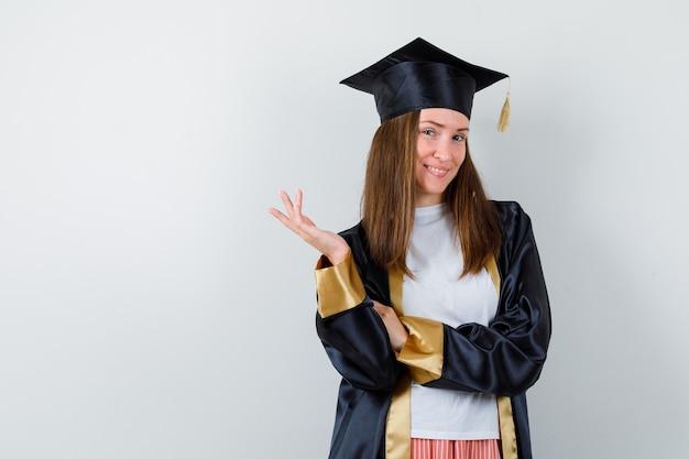Portret van vrouwelijke afgestudeerde poseren terwijl het verhogen hand in uniforme, vrijetijdskleding en op zoek charmant vooraanzicht