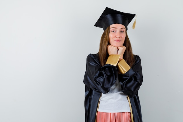 Portret van vrouwelijke afgestudeerde propping kin op vuisten in uniforme, vrijetijdskleding en op zoek naar intelligent vooraanzicht