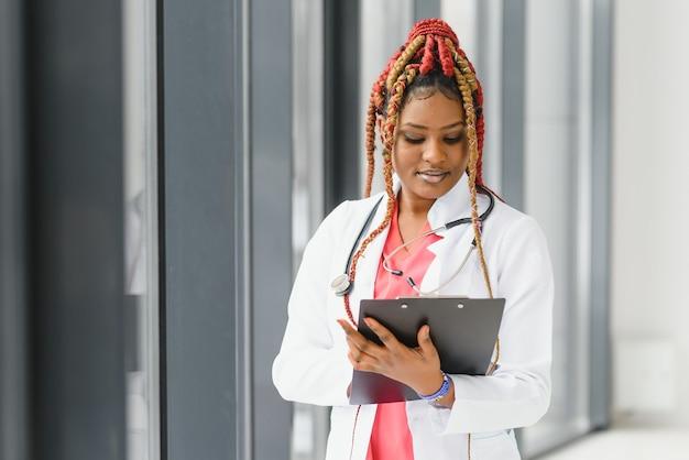 Portret van vrouwelijke afrikaanse amerikaanse arts die zich in haar bureau bij kliniek bevindt