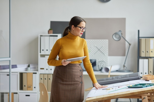 Portret van vrouwelijke architect blauwdrukken kijken tijdens het werken aan de tekentafel in kantoor,