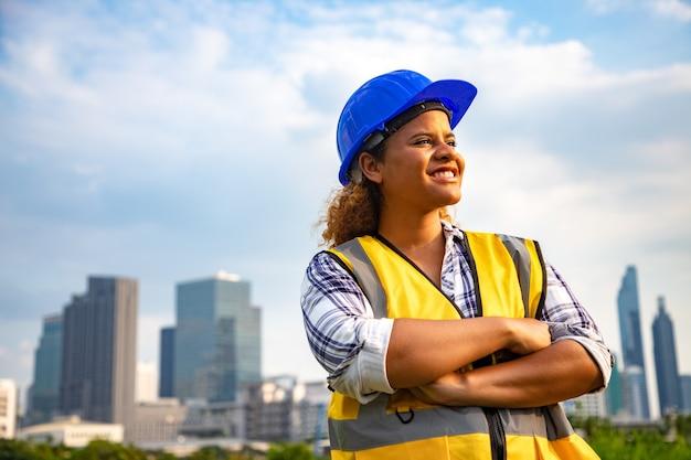 Portret van vrouwelijke architect permanent en draag bouwvakker in het openbare park.