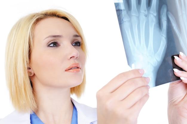 Portret van vrouwelijke arts die de medische x-ray toont - die op wit wordt geïsoleerd