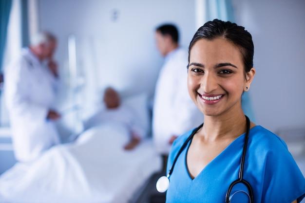 Portret van vrouwelijke arts die in de afdeling glimlacht